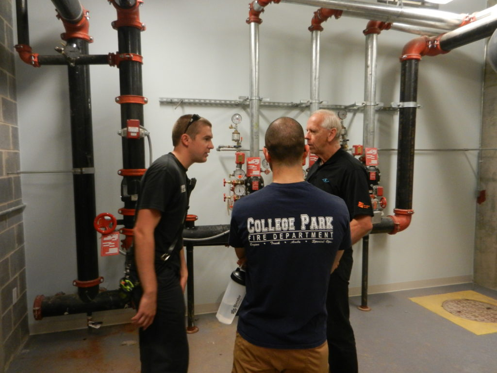 Figure 6. Firefighters learning about a building's sprinkler and standpipe systems with the help of the building maintenance staff. Photo by author.